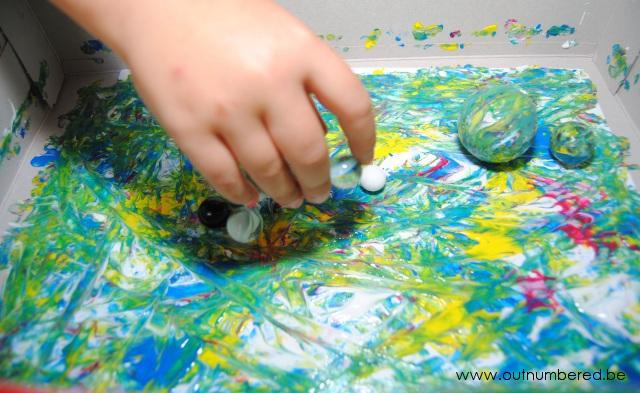 Kind schildert met knikkers in een kartonnen doos