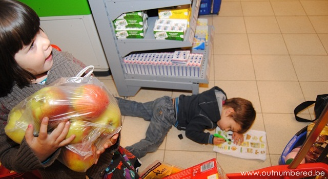 kid helps to put the shoppings on the band