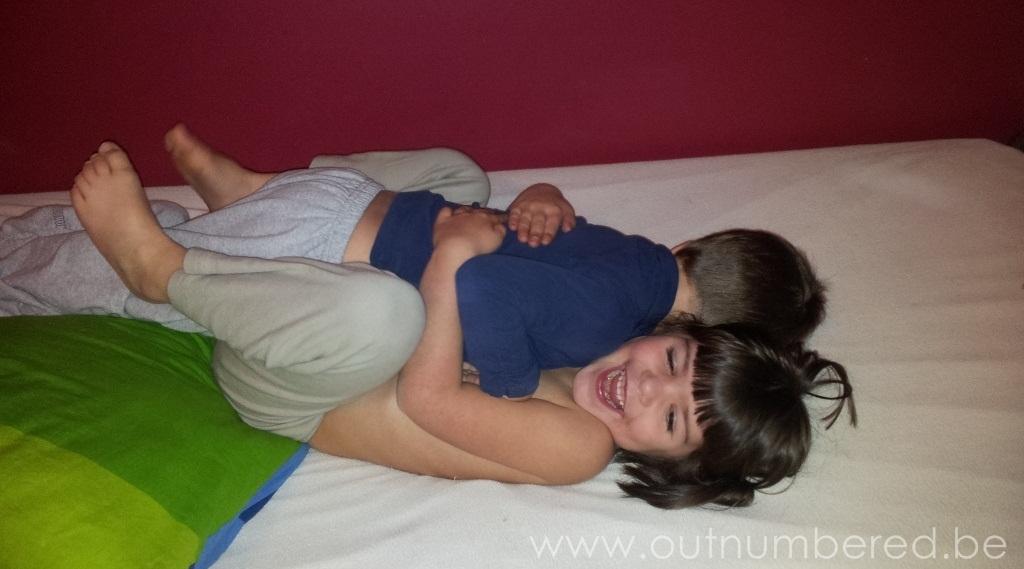 Broer en zus spelen en knuffelen in bed